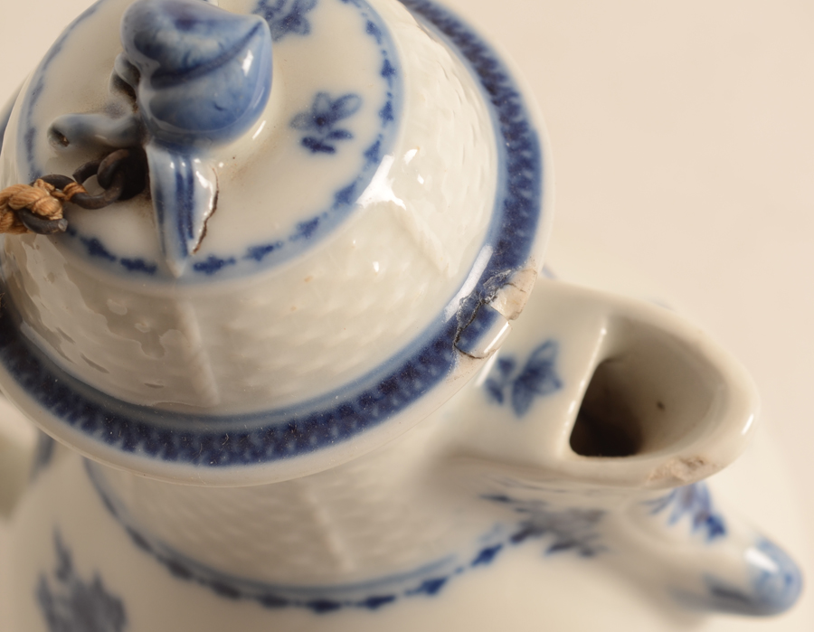 Small blue-white coffee pot china — Detail of the chips to the spout and lid.