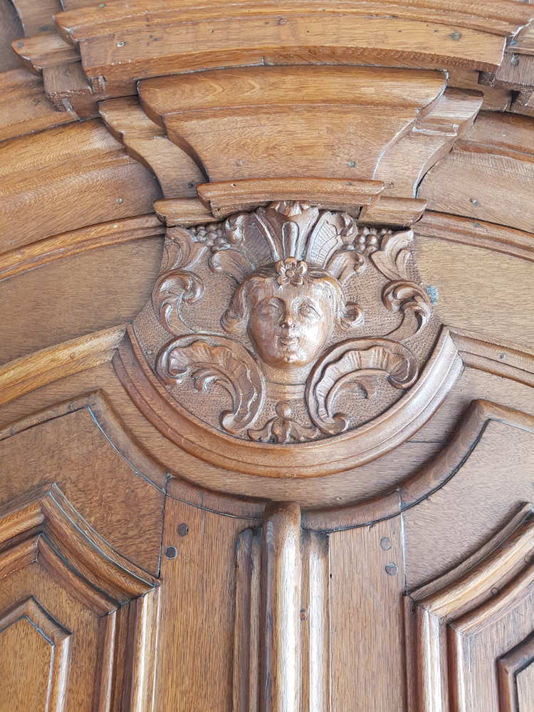 Flemish regence armoire — the central motif above the doors