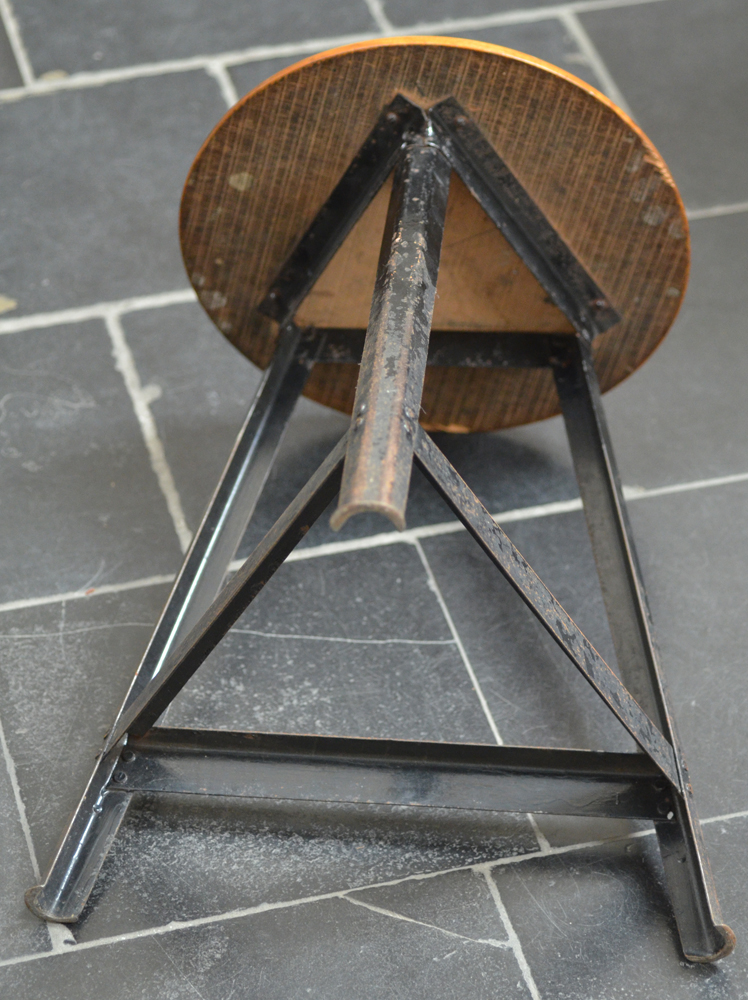 An industrial stool 1950's — view from below, joints at the base rivetted.