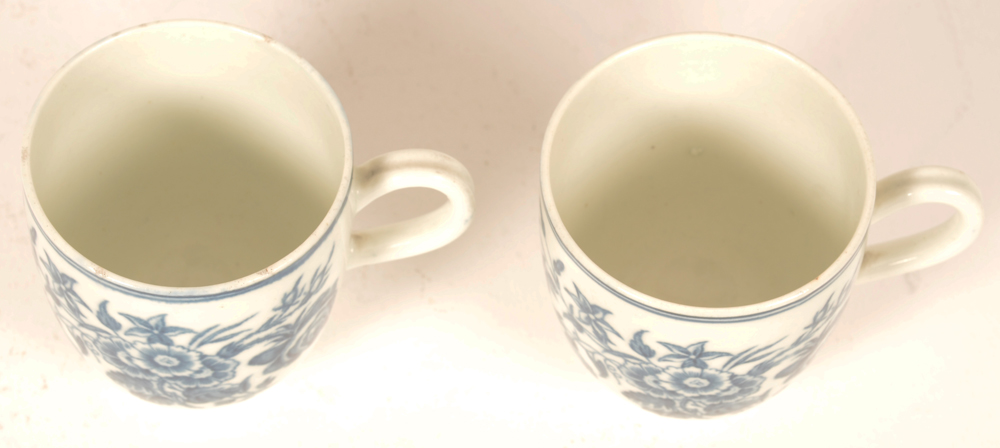 2 18th century Worcester porcelain cups — the three flowers pattern in underglaze transfer printed blue, with delicately shaped handles